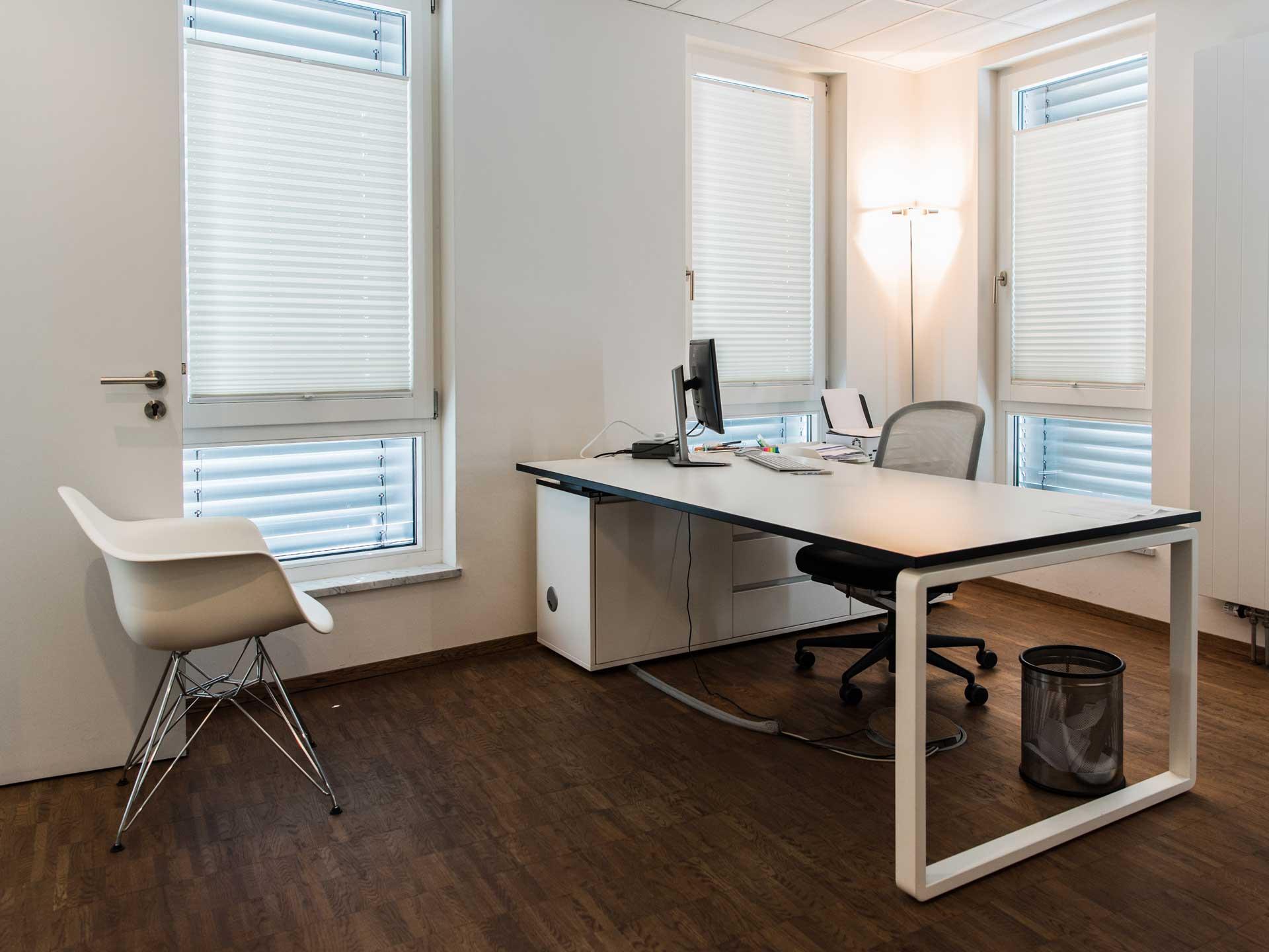 Praxis Dr. Frommlet Untersuchungsraum mit Schreibtisch