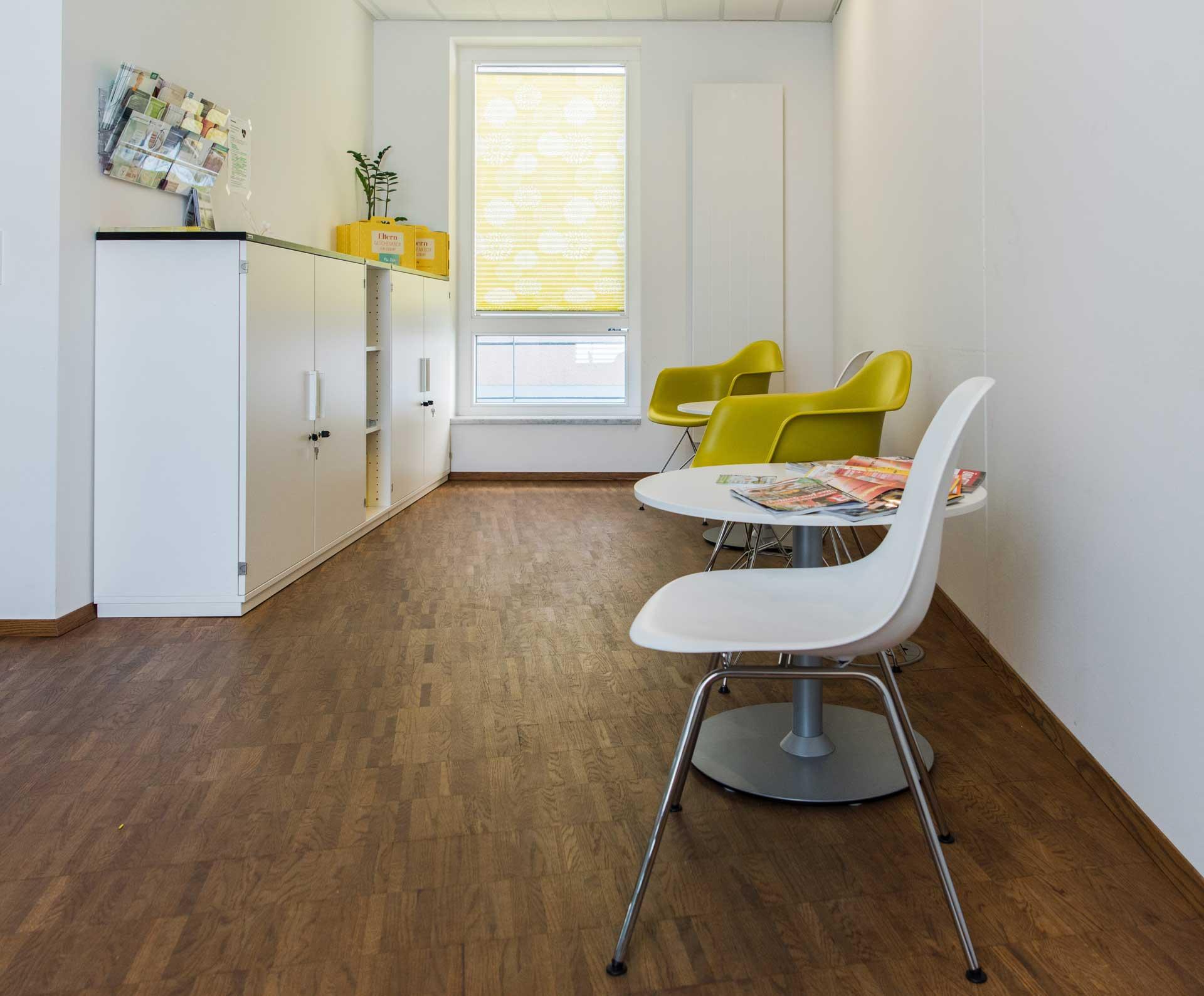 Praxis Dr. Frommlet Wartezimmer mit grünem und weissen Stühlen
