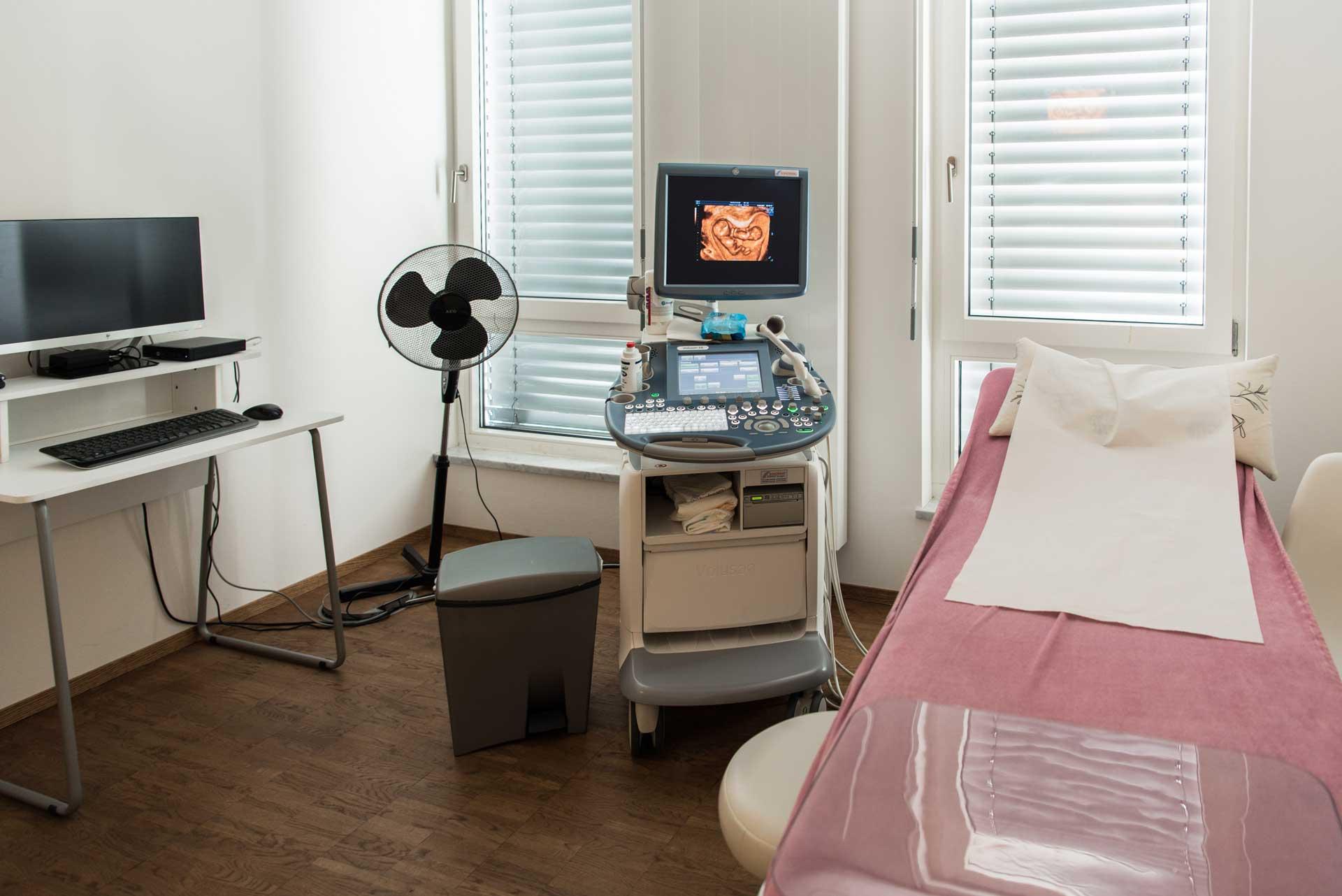 Praxis Dr. Frommlet Untersuchungsraum mit Ultraschallgerät und Liege